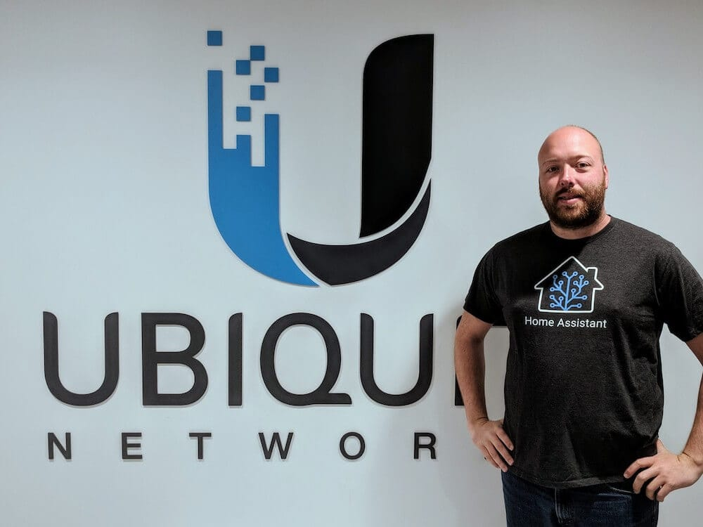Photo of Paulus, the founder of Home Assistant, standing in front of a Ubiquiti Networks logo wearing a Home Assistant t-shirt.